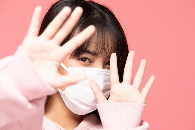 Młoda kobieta azji noszenie maski ochronnej lub maski chirurgicznej dla chronionego wirusa i zanieczyszczenia powietrza, dzięki czemu ręka zatrzymać wirusa na różowej ścianie, koncepcji opieki zdrowotnej i koronawirusa