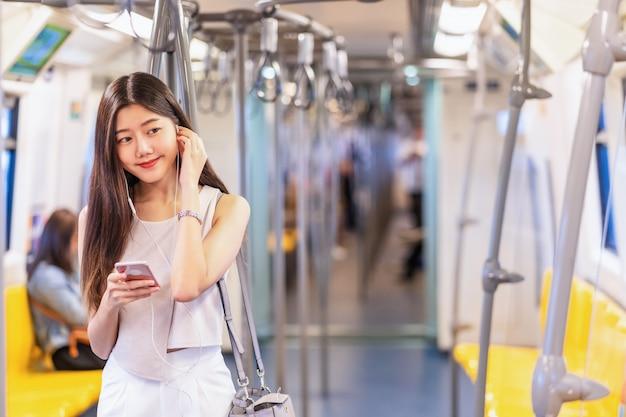Młoda kobieta azji pasażer słucha muzyki za pomocą inteligentnego telefonu komórkowego w pociągu metra podczas podróży w wielkim mieście, japońskim, chińskim, koreańskim stylu życia i codziennego życia, dojazdy do pracy i transport