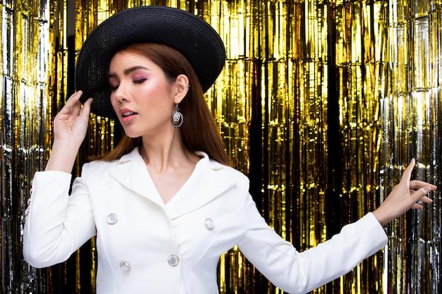 Młoda kobieta azji piękne mody nosić białą marynarkę garnitur sukienka z kapeluszem w czasie party rocznica nowy rok. oświetlenie studyjne złota folia kurtyna przestrzeń kopii w tle