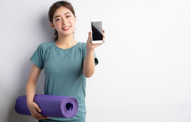Młoda kobieta azji robi ćwiczenia na białym tle