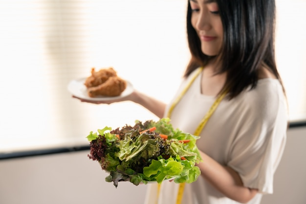 Młoda kobieta azji schudnąć, wybierając między sałatka jarzynowa i fast foodów smażonego kurczaka w naczyniach na rękę
