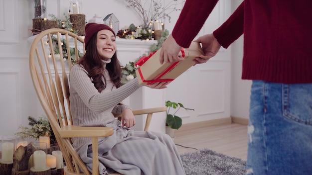 Młoda kobieta azji siedzi na krześle owinięty w szary koc w jej salonie w domu.
