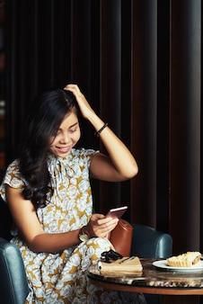 Młoda kobieta azji siedzi w kawiarni, patrząc na smartfona i śmiejąc się
