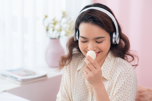 Młoda kobieta azji, słuchanie muzyki i ciesząc makaronik