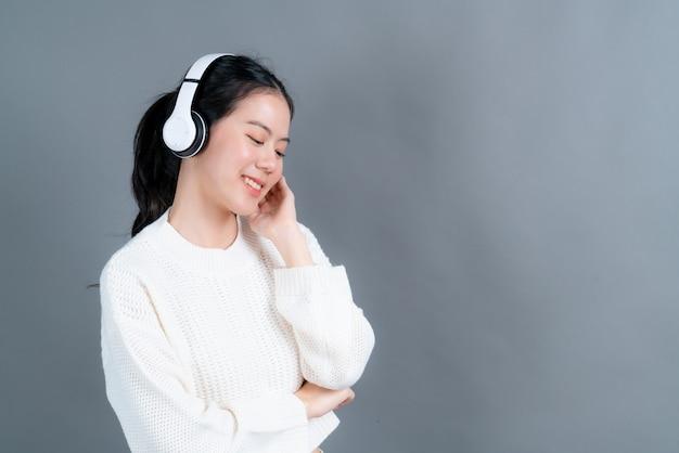 Młoda kobieta azji słuchanie muzyki i słuchanie muzyki w słuchawkach na szarej ścianie