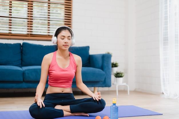 Młoda kobieta azji słuchanie muzyki podczas uprawiania jogi w salonie