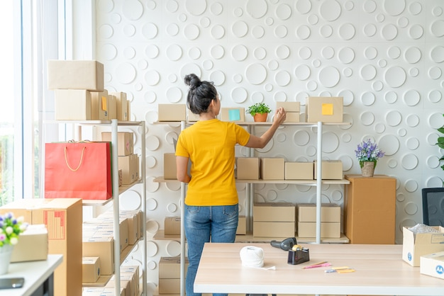 Młoda kobieta azji sprawdzanie towarów na półce w magazynie - koncepcja sprzedaży lub zakupów online