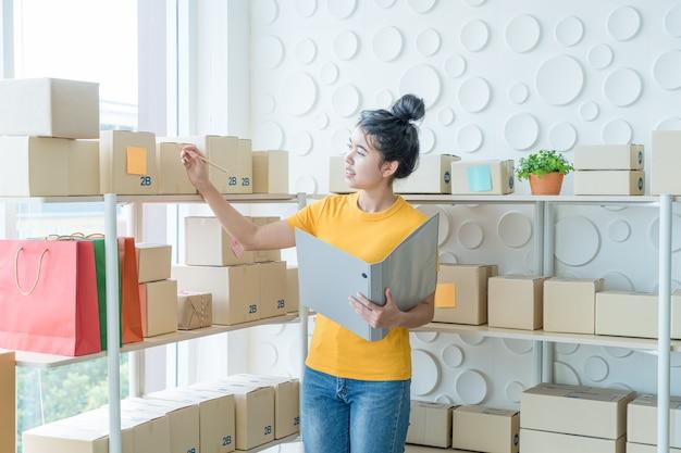 Młoda kobieta azji sprawdzanie towarów na półce w magazynie