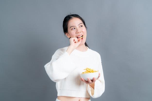 Młoda kobieta azji w biały sweter je chipsy ziemniaczane na szarym tle