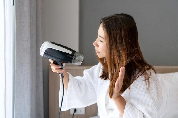 Młoda kobieta azji w biały szlafrok cios suszenie włosów rano