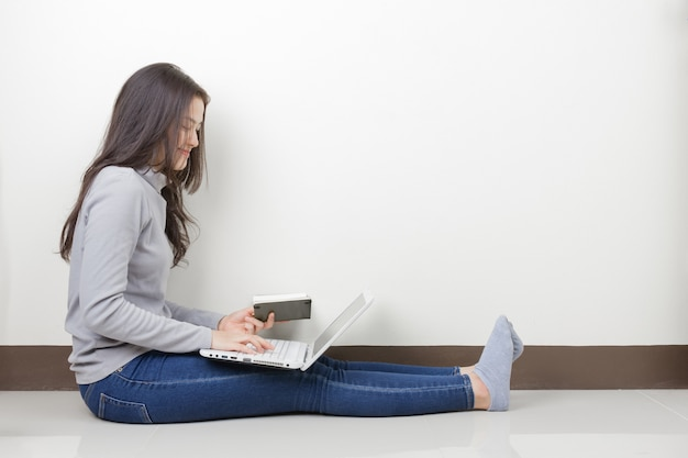 Młoda kobieta azji w okularach i laptopie siedzi w pokoju. szczęśliwa buźka.
