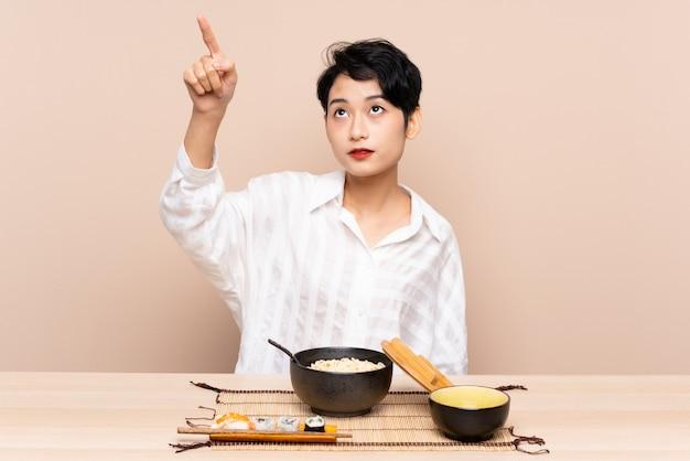 Młoda kobieta azji w tabeli z miską makaronu i sushi dotykając przezroczystego ekranu