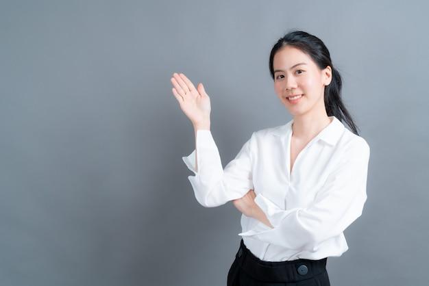 Młoda kobieta azji z ręką prezentacji na stronie