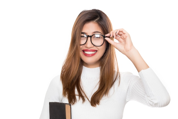 Młoda kobieta azji z uśmiechniętą buźkę w okularach z ręki trzymającej książkę na białym tle.
