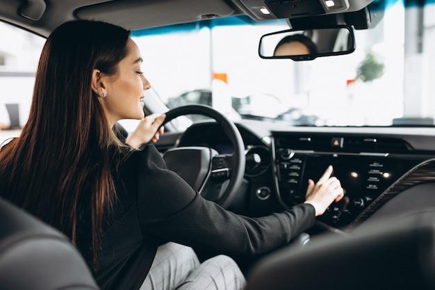 Młoda kobieta bada samochód w samochodowej sala wystawowej