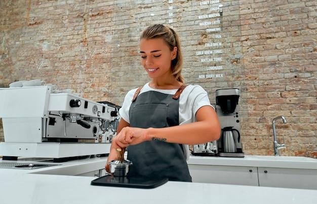 Młoda kobieta barista naciska zmieloną kawę za pomocą ubijaka w kawiarni.