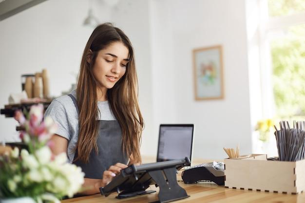 Młoda kobieta barista prowadzi kawiarnię za pomocą terminala płatniczego i laptopa.