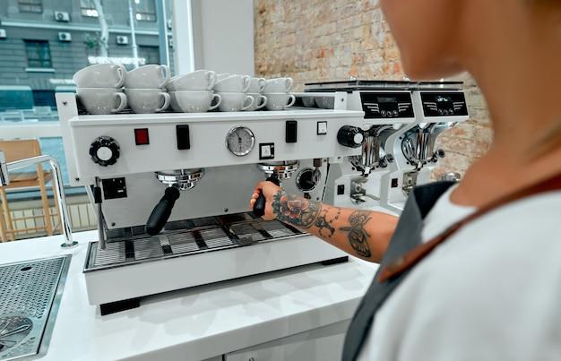 Młoda kobieta barista przygotowuje kawę dla klienta na ekspres do kawy w kawiarni.