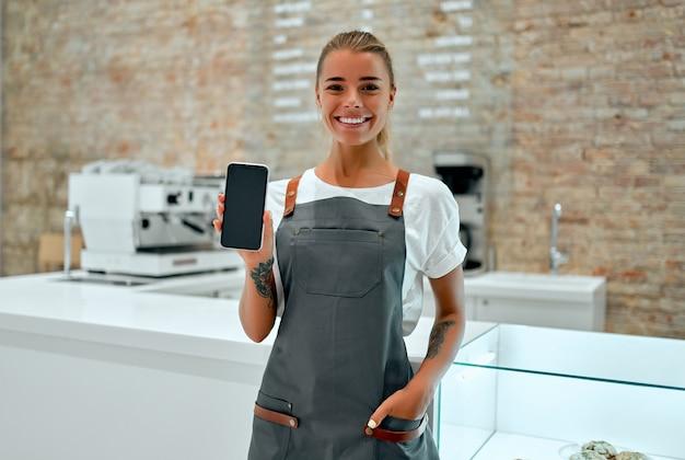 Młoda kobieta barista stoi przy ladzie w kawiarni i uśmiecha się, pokazując pusty ekran smartfona.