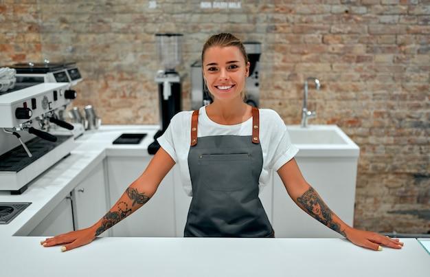 Młoda kobieta barista stoi przy ladzie w kawiarni i uśmiecha się.