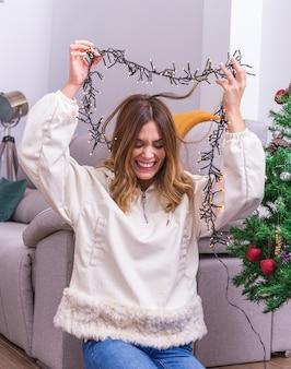 Młoda kobieta bawi się dekorowaniem choinki. wesołych świąt i szczęśliwego nowego roku koncepcja. wesołych świąt. miejsce na tekst