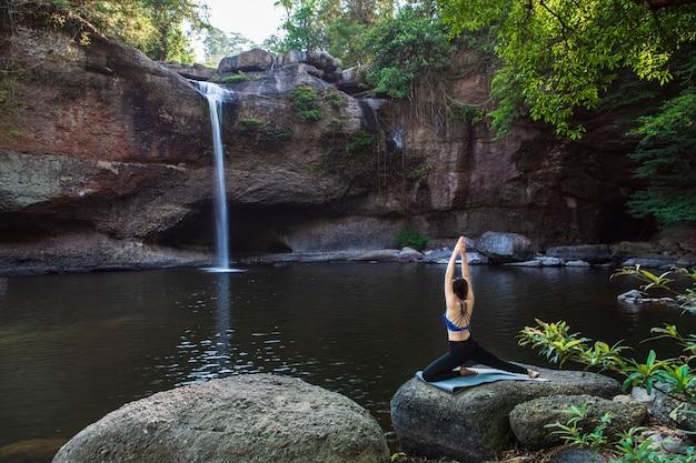 Młoda kobieta bawi się jogą przed wodospadem