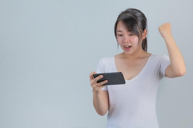 Młoda kobieta bawi się telefonem pokazującym radość na szarej ścianie