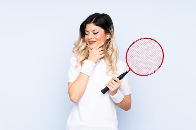 Młoda kobieta bawić się badminton odizolowywającego na błękit ścianie myśleć pomysł