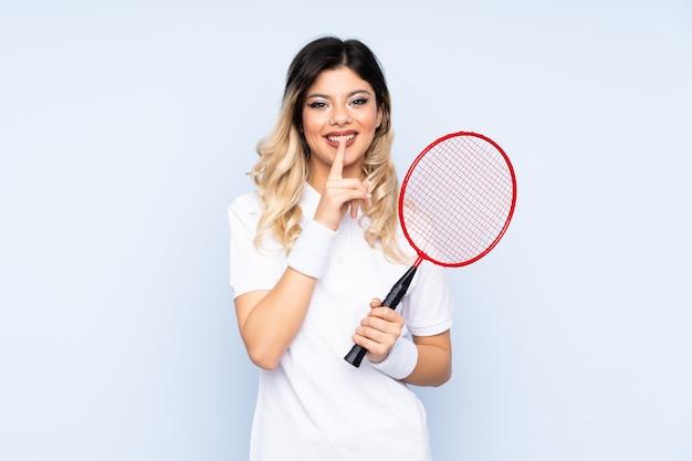 Młoda kobieta bawić się badminton odizolowywającego na błękit ścianie robi cisza gestowi