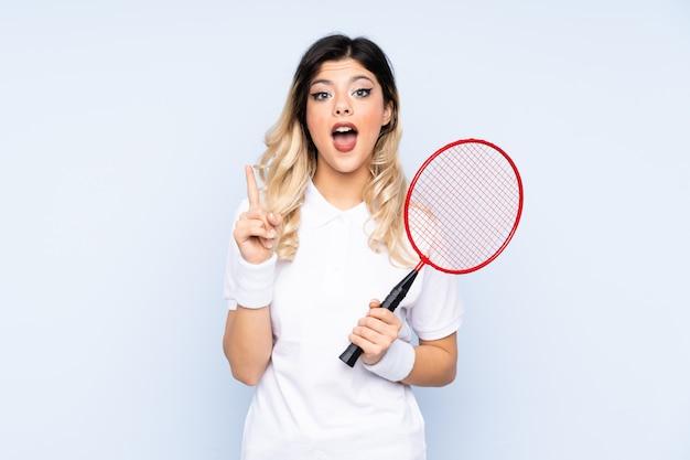 Młoda kobieta bawić się badminton odizolowywającego na błękit ścianie z niespodzianka wyrazem twarzy