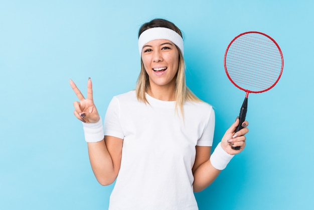 Młoda kobieta bawić się badminton odizolowywał radosnego i beztroskiego pokazywać pokoju symbol z palcami