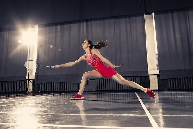 Młoda kobieta bawić się badminton przy gym