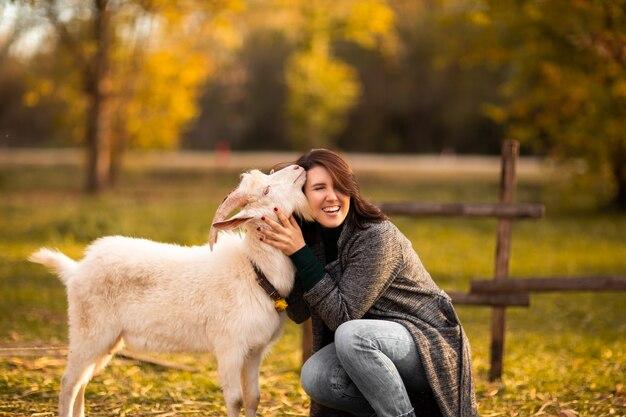 Młoda kobieta bawić się z białą kózką na bani gospodarstwie rolnym. jesieni tło.