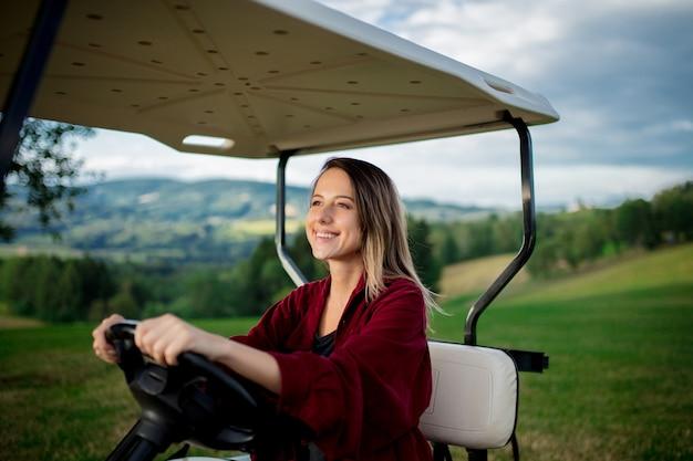 Młoda kobieta bawić się z golfowym buggy samochodem na polu w górach