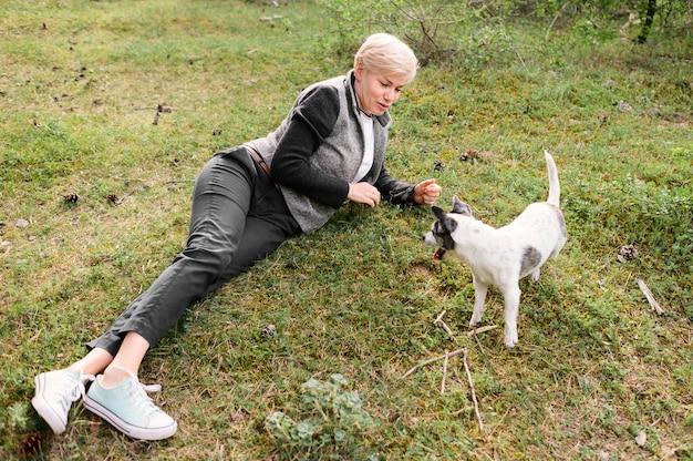 Młoda kobieta bawić się z jej psem outdoors
