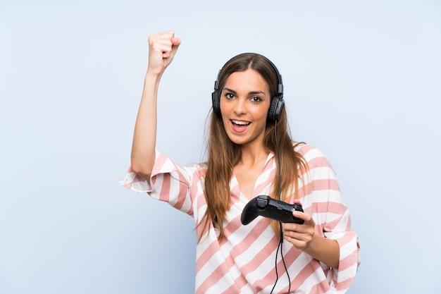 Młoda kobieta bawić się z kontrolerem gier wideo nad odosobnioną błękit ścianą świętuje zwycięstwo