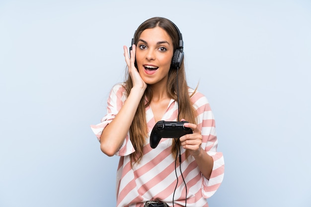 Młoda kobieta bawić się z kontrolerem gier wideo nad odosobnioną błękit ścianą z niespodzianką i zszokowanym wyrazem twarzy
