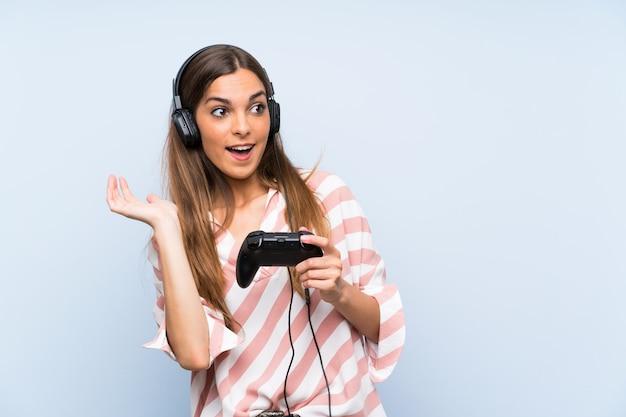 Młoda kobieta bawić się z kontrolerem gier wideo nad odosobnioną błękit ścianą z niespodzianka wyrazem twarzy