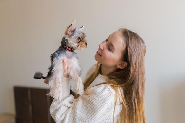 Młoda kobieta bawić się z psem w weekend w domu. szczęśliwy szczeniak yorkshire terrier
