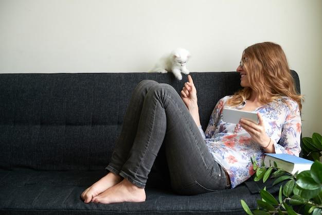 Młoda kobieta bawić się z puszystym białego kociaka horyzontalnym strzałem