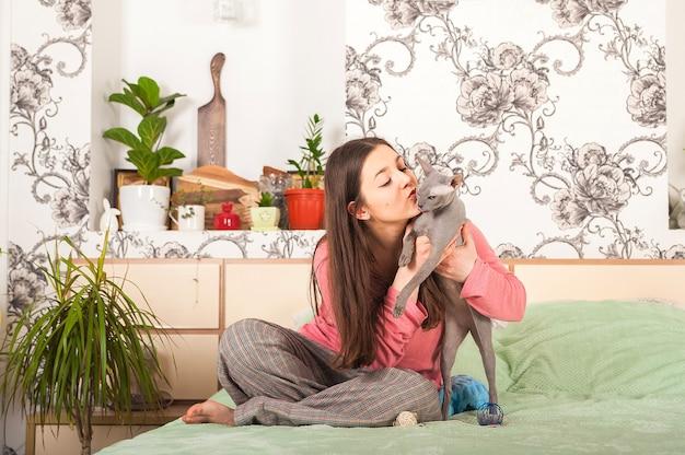 Młoda kobieta bawić się z sfinksa w domu close-up i kopii przestrzenią. zwierzęta i ludzie.