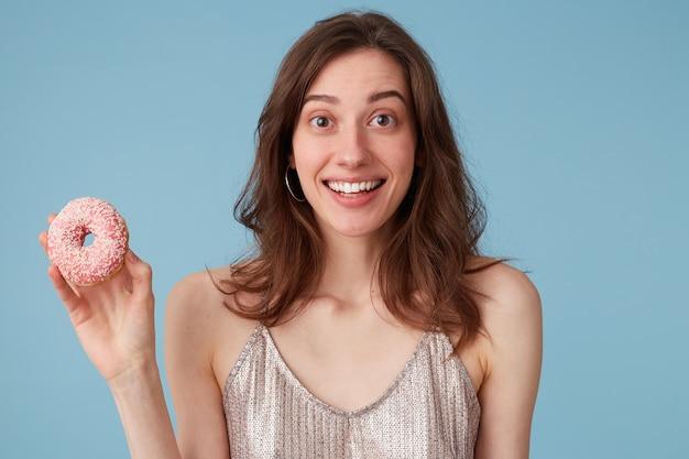 Młoda kobieta będzie jeść słodki różowy pączek, który trzyma w ręku