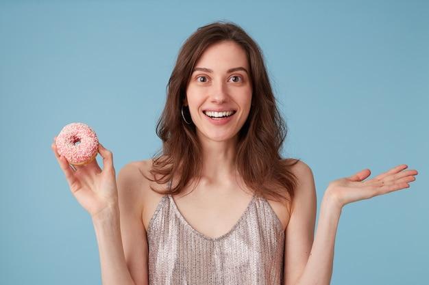 Młoda kobieta będzie jeść słodki różowy pączek trzyma go w ręku na odosobnionej niebieskiej ścianie