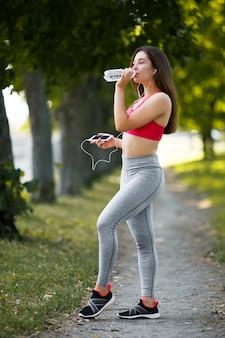 Młoda kobieta biega outdoors w parku.