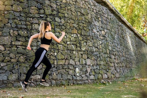 Młoda kobieta biega outdoors z odzieżą sportową