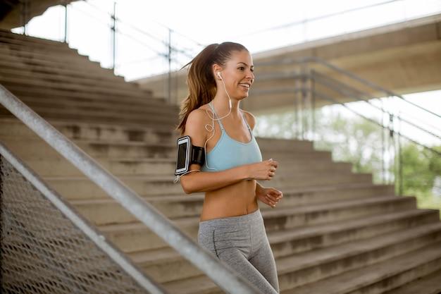 Młoda kobieta biega samotnie w dół schodki plenerowych w miastowym środowisku