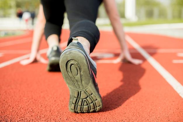 Młoda kobieta biegacz przygotowuje się do uruchomienia na torze