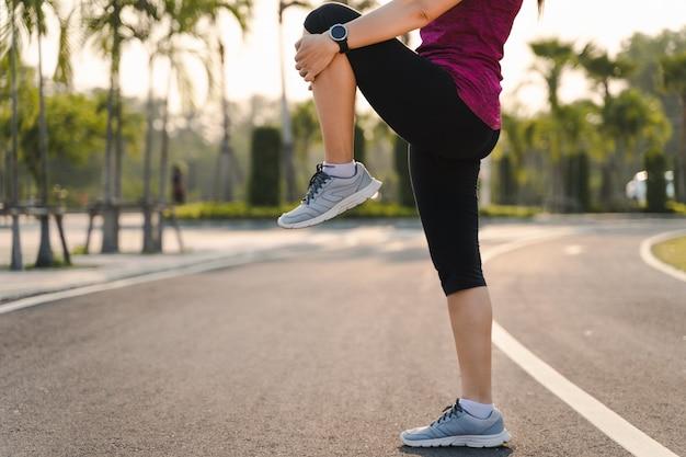 Młoda kobieta biegacz rozciąganie nogi przed uruchomieniem w parku.