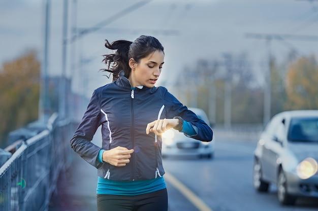 Młoda kobieta biegacz sprawdzanie czasu z inteligentnego zegarka
