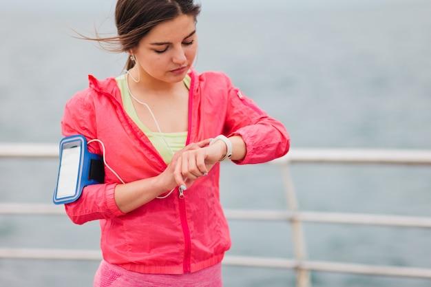 Młoda kobieta biegacz w odzieży sportowej używa inteligentnego urządzenia śledzącego na plaży.